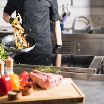 Koch schwenkt Gemüse in einer Pfanne